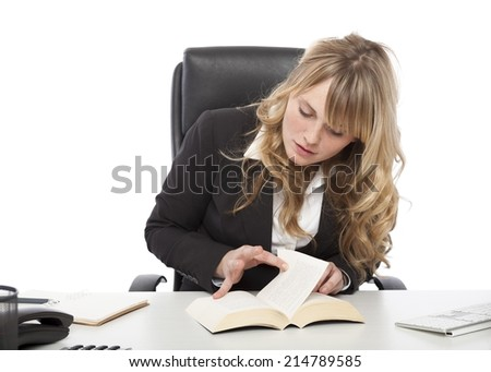 Young businesswoman paging through a book at her desk as she tries to find the answer to a problem or locate specific information - stock photo