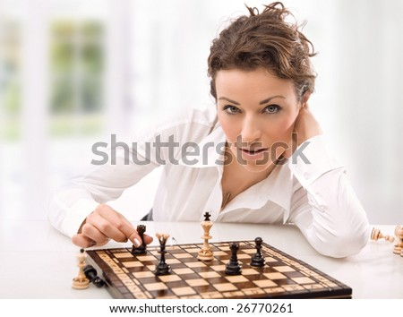 Young businesswoman playing chess - stock photo
