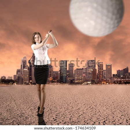 Young businesswoman playing golf in the town - stock photo