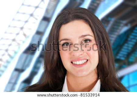 Young businesswoman portrait with a glass building in the background - stock photo