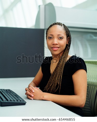 Young businesswoman posing at computer keyboard - stock photo