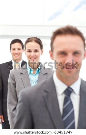 Young businesswoman posing with two businessmen in a row at work