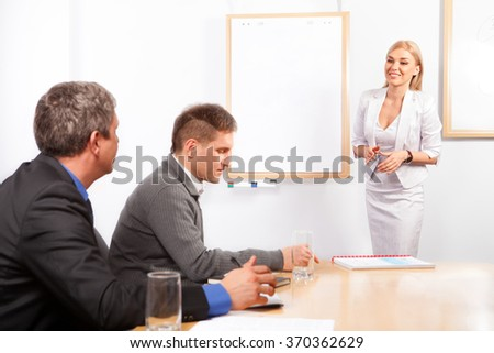 Young Businesswoman Presenting His Ideas on Flip Chart to Colleagues - stock photo