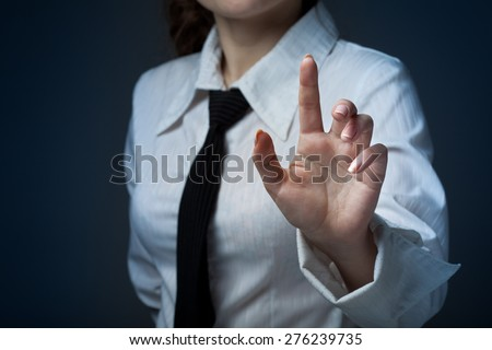 Young businesswoman pressing high tech type of modern buttons - stock photo