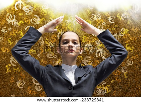 Young businesswoman protecting head from falling symbols - stock photo