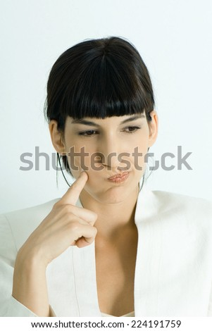 Young businesswoman puffing cheeks out, holding finger to cheek, looking away, portrait