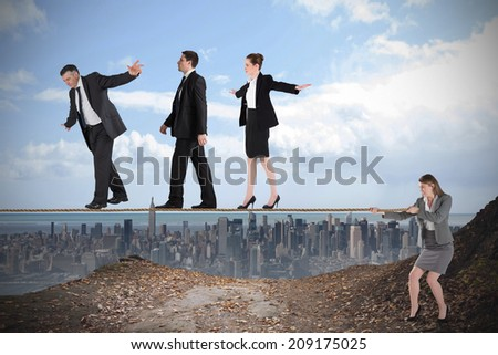 Young businesswoman pulling a tightrope for business people against large city on the horizon - stock photo