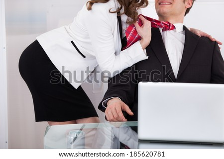 Young businesswoman pulling male colleague's tie while seducing him at desk in office - stock photo