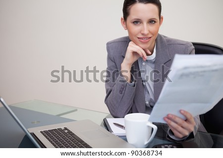 Young businesswoman reading company's notification