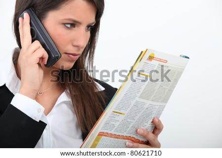 Young businesswoman reading magazine whilst telephoning - stock photo