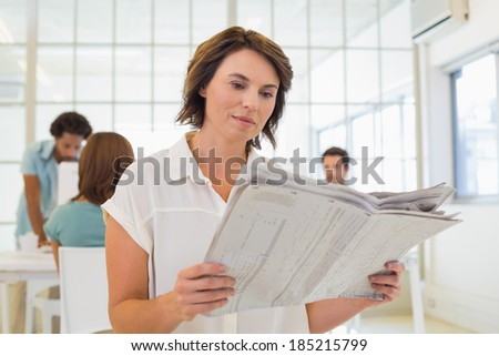 Young businesswoman reading newspaper with colleagues in meeting in background at the office - stock photo
