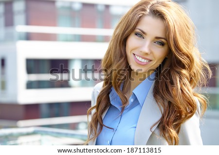 Young businesswoman (real estate agent) presenting detached modern houses - stock photo