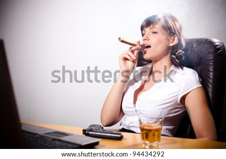 Young businesswoman relaxing in her office. Smoking a fat cigar and drinking whiskey.