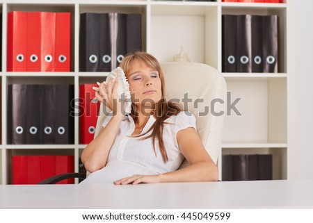 Young businesswoman rests at the table at the office. Timeout.