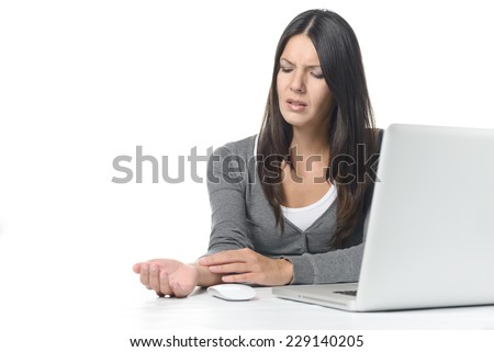 Young businesswoman rubbing and massaging her wrist to relieve cramps after using a computer mouse for too long at a stretch, on white - stock photo
