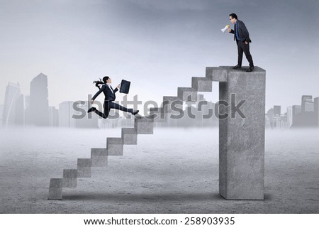 Young businesswoman running on the stair to meet her colleague on the top