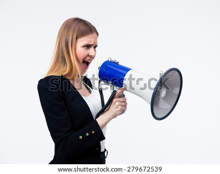 Young businesswoman screaming in megaphone over gray background - stock photo