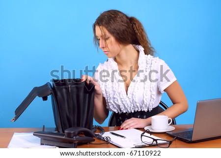 Young businesswoman searching some document in briefcase at the office - stock photo