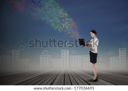 Young businesswoman sending e-mail with a laptop - stock photo