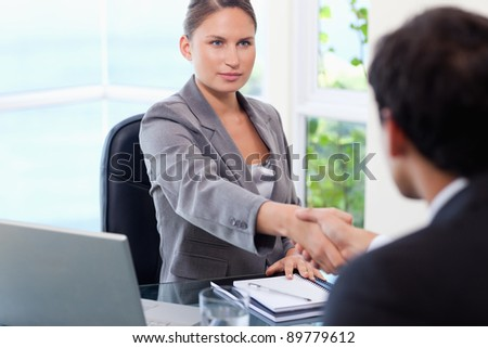 Young businesswoman shaking hands with customer - stock photo