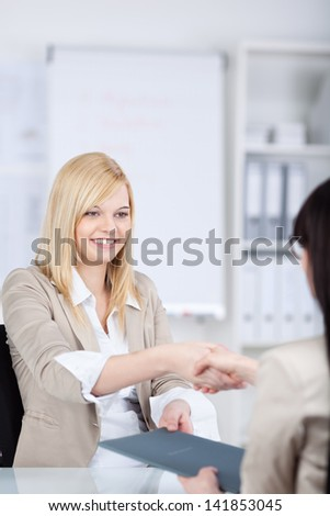 Young businesswoman shaking hands with female candidate at office desk - stock photo