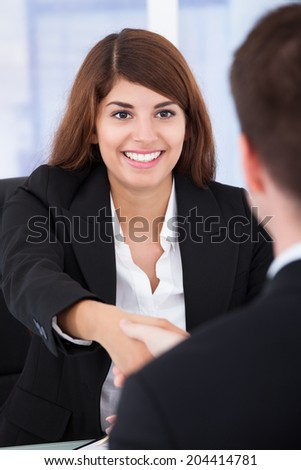 Young businesswoman shaking hands with male partner in office - stock photo