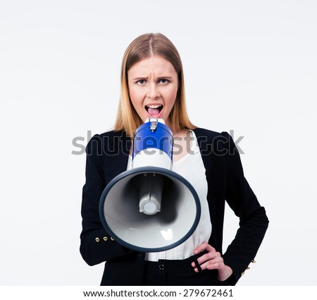 Young businesswoman shouting in megaphone at camera. Isolated on a gray background - stock photo