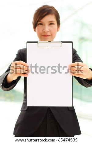 Young businesswoman showing clipboard