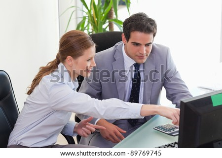 Young businesswoman showing her colleague something on the screen - stock photo