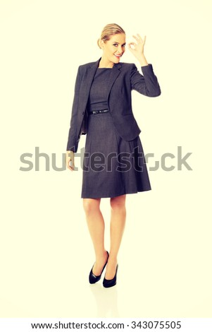 Young businesswoman showing ok sign - stock photo