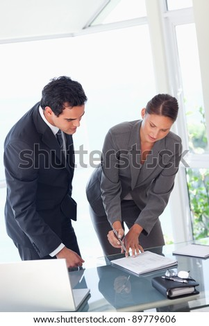 Young businesswoman showing partner where to sign - stock photo