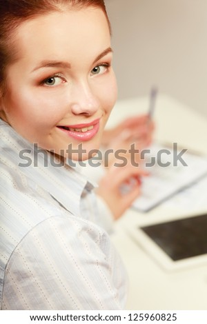 Young businesswoman signing documents at desk - stock photo