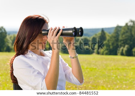 Young businesswoman sit sunny meadow on armchair seeking binocular