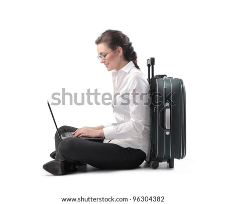 Young businesswoman sitting against a suitcase and using a laptop - stock photo