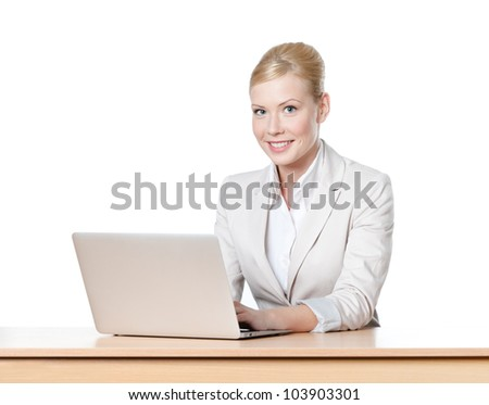 Young businesswoman sitting at a office table with laptop, looking at the camera - stock photo