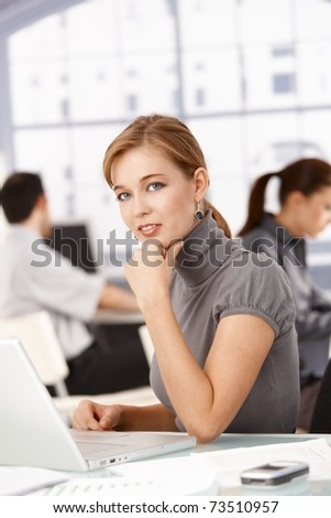 Young businesswoman sitting at desk in office working on laptop, colleagues working in the background. - stock photo