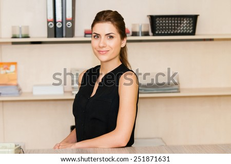 Young businesswoman sitting at desk smiling and looking at camera - stock photo