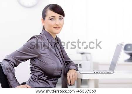 Young businesswoman sitting at office desk, using laptop computer, looking at camera, smiling.