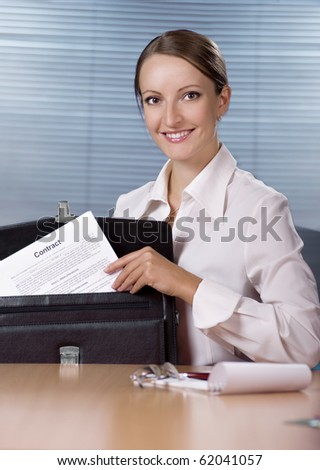 Young businesswoman sitting at the desk in office and holding contract document in briefcase