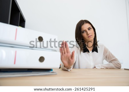 Young businesswoman sitting at the table and saying - No - stock photo