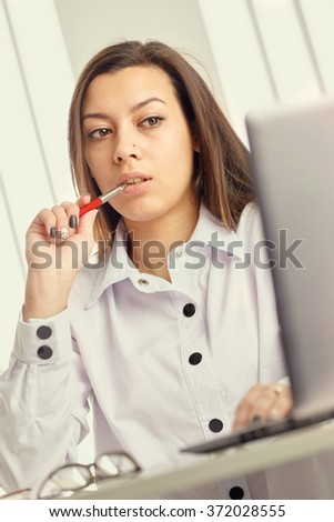 Young businesswoman sitting at the table, holding a pen, looking at the laptop. - stock photo