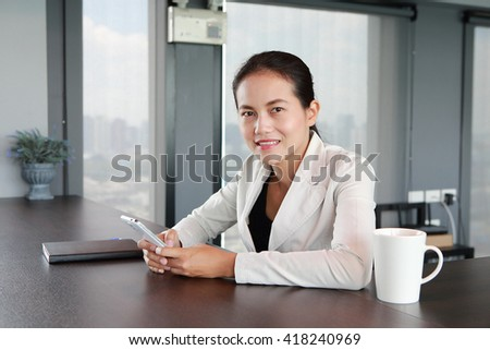 Young businesswoman sitting at the table on workplace in office using the smart phone and looking directly