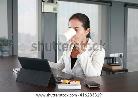 Young businesswoman sitting at the table on workplace in office with laptop computer drinking a coffee