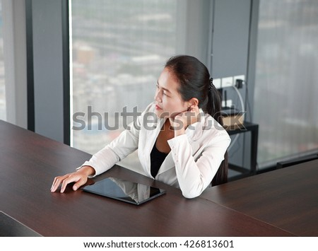Young businesswoman sitting at the table on workplace in office with tablet and look out