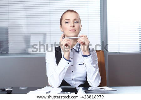 Young businesswoman sitting at workplace - stock photo