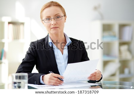 Young businesswoman sitting at workplace and looking at camera in office - stock photo