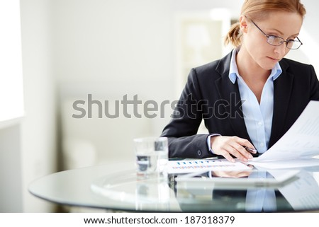 Young businesswoman sitting at workplace and reading paper in office - stock photo