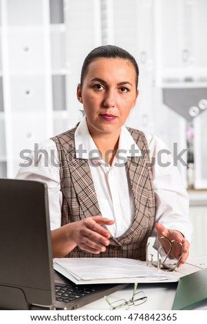 Young businesswoman sitting at workplace and working with papers in office.