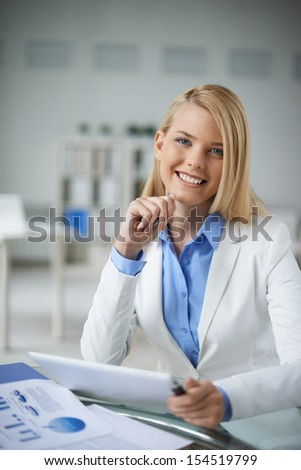 Young businesswoman sitting at workplace in office and looking at camera