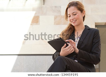 Young businesswoman sitting down on stone steps in a modern city with office buildings using a digital tablet pad, smiling.